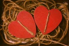 Rouges ficelle entrelacée deux par coeurs fond romantique Images stock