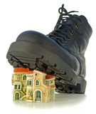 Rough boot treads on houses. Rough boot on a high thick sole treads on houses Royalty Free Stock Images