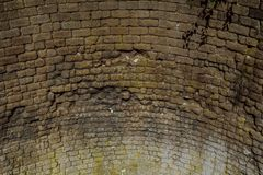 Rough brick curved wall from the middle ages. Old weathered brick semicircular wallninside of historic lime kiln royalty free stock image