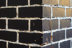 Rough brick wall. Painted in black with painting seams in white. Abstract background Stock Image