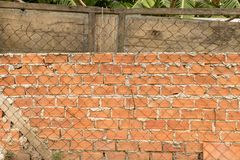 Rough Brick Wall with Rusty Wire Fence and Old Wooden Door in the Garden stock image