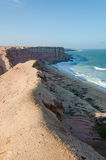 Rough coast line with towering cliffs and wild ocean in Angola. `s Namib Desert Stock Images
