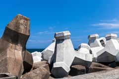Rough concrete breakwater blocks are under cloudy sky. Industrial background photo royalty free stock photography