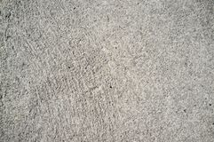 Rough concrete wall texture with small, grey rocks embedded in surface royalty free stock image
