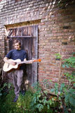 Rough country guy playing his guitar. In the backyard Royalty Free Stock Photo