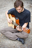 Rough country guy playing his guitar. In the backyard Royalty Free Stock Images