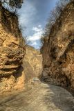 Rough dirt road turns into a paved road in a close canyon with bright blue sky. Outside of Beijing royalty free stock photography