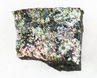 Rough dunite stone on white. Macro shooting of natural mineral rock specimen - rough dunite stone on white marble background Stock Photo
