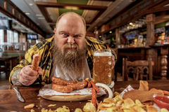 Rough fat male tasting frankfurters in pub Royalty Free Stock Images
