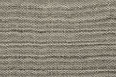 Rough grained texture fabric of beige color. Grained texture of textile rough fabric of beige color for empty and pure backgrounds stock images