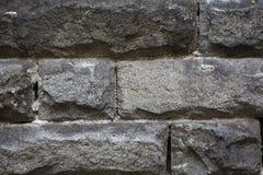 Rough granite stone wall. Closeup of rough granite stone brick wall background Stock Images