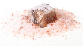 Rough Halite mineral in pink Himalayan Salt. Rough Halite mineral in pile of grained pink Himalayan Salt on white background royalty free stock images