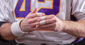 Rough Hands Of American footballer. Taped fingers Of American footballer royalty free stock photography