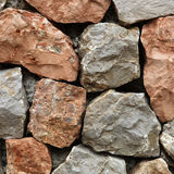 Rough hewn stone forming a wall. Large rough hewn natural stones and rocks interlocked without mortar forming a garden wall Stock Photos