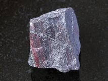 rough jaspilite (ferruginous quartzite) on dark stock photo