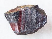 Rough jaspilite stone on white. Macro shooting of natural mineral rock specimen - rough jaspilite (ferruginous quartzite) stone on white marble background royalty free stock image