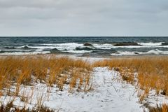 Rough lake and snow covered winter shoreline. Rough, stormy lake and snow covered winter shoreline in Michigan Royalty Free Stock Photography