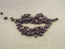 On rough linen canvas applique from roasted coffee beans in the shape of the lips of the mouth of a person. Smile. Applique from beans roasted coffee in the Stock Images