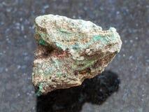 Rough Malachite (copper ore) stone on dark. Macro shooting of natural mineral rock specimen - rough Malachite (copper ore) stone on dark granite background royalty free stock photo