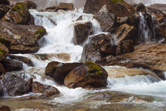 Rough mountain river with waterfall. Rough mountain river with a waterfall flowing between rocks royalty free stock photos