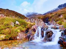 The rough mountain stream in the mountains. Snowy cone of mountain in clouds. Dry grass and heather bushes on banks Royalty Free Stock Images