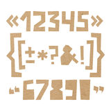 Rough numbers and symbols cut out of paper on cardboard background. Rough numbers and symbols including brackets, curly braces, exclamation and question marks Stock Photo
