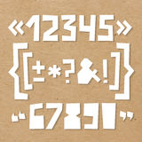 Rough numbers and symbols cut out of paper on cardboard. Rough numbers and symbols including brackets, curly braces, exclamation and question marks, quotation Royalty Free Stock Photos