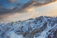 Shorebreak wave at sunset time. Rough ocean wave with white foam closeup shot Royalty Free Stock Photos