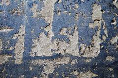 Rough painted concrete surface. Damaged concrete surface with holes and illegible inscription partially covered with blue paint Stock Image