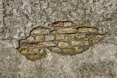 Rough plaster revealing brickwork. Grungy and irregular old plaster wall with a large hole revealing red, yellow and white brickwork Stock Photography