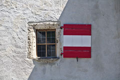Rough plastered castle wall with window and wooden shutters colored like the Austrian flag, partly in the shade Royalty Free Stock Photos