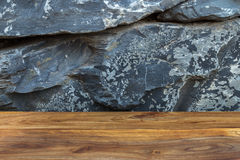 Rough reddish brown wood board with exotic natural stonewall as Stock Photo