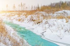 Rough river at the foot of the mountains in a turquoise, blue, green forest in winter, ice and snow around the landscape. royalty free stock photo