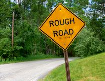 Rough road ahead sign. A caution rough road sign on a rural road with a sarcastic comment stock photography