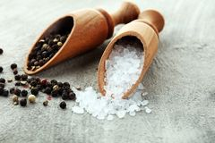 Rough salt and mixed peppercorns on wooden shovels.  stock photo