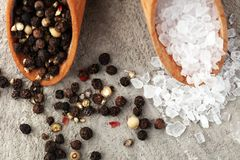 Rough salt and mixed peppercorns on wooden shovels.  royalty free stock photo