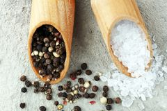 Rough salt and mixed peppercorns on wooden shovels.  stock images