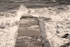 Rough sea covering a cement pier Stock Photo