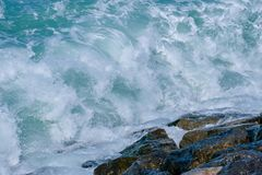 Rough sea and high waves. Crashing on shore aginst rocks boulder boulders danger ocean warning windy royalty free stock photo