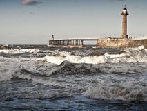 Rough sea with pier in whitby Stock Images
