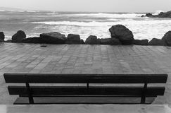 Rough sea by the promenade. Rough sea and an empty bench Royalty Free Stock Photography