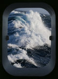 Rough sea through a ships porthole. View of rough sea through a ships porthole - North Atlantic Ocean royalty free stock images