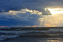 Rough Sea at Sunset. Rough water and dark threatening clouds accent streams of light beams from the setting sun Stock Images