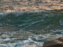 Rough sea at sunset Stock Images