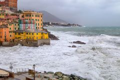 Rough sea in the village of Genoa Boccadasse with colorful houses, Italy. royalty free stock photos