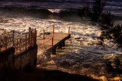 Rough Sea Waves Crashing On Old Pier Stock Photos