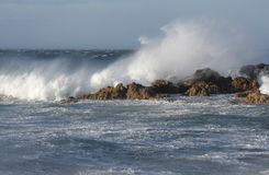Rough seas. With waves breaking over some rocks Stock Image