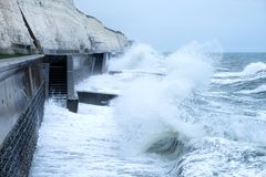 Free Rough Seas Crashing Against Brighton Sea Wall With Cliffs Behind Royalty Free Stock Image - 120051656