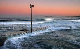 Rough seas flowing. Over a tidal pool at twilight royalty free stock photography