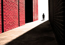 Rough skin. Processed photograph of a distant boy next to a brick wall. Used to illustrate a single child's strength, challenges and fear Royalty Free Stock Image